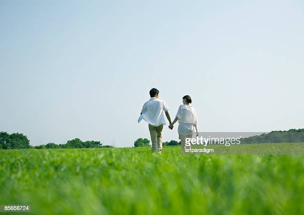 Young couple taking a walk on grass