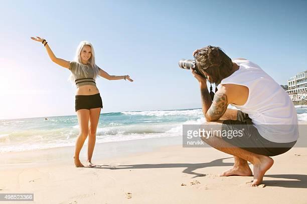 Jeune couple prenant des photos sur la plage