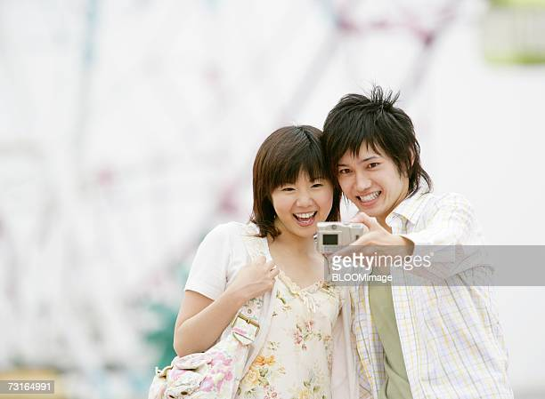 Young couple taking picture in the amusement park