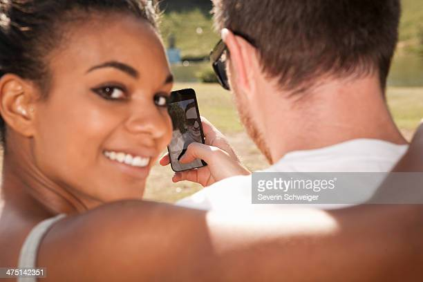 Young couple taking picture of themselves with phone, woman looking over shoulder