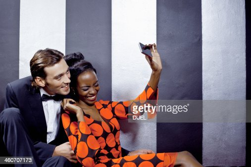 Young couple taking self portrait in nightclub : Stock Photo