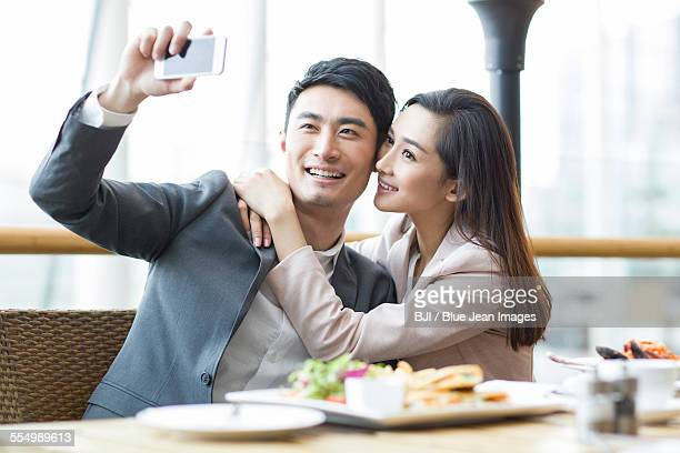 Young couple taking self portrait in restaurant
