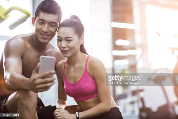 Young couple taking self portrait in the gym