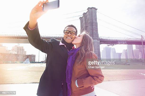 Young couple taking self portrait next to Brooklyn Bridge, New York, USA