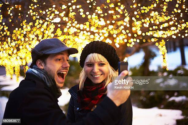 Young couple taking self portrait with outdoor xmas lights