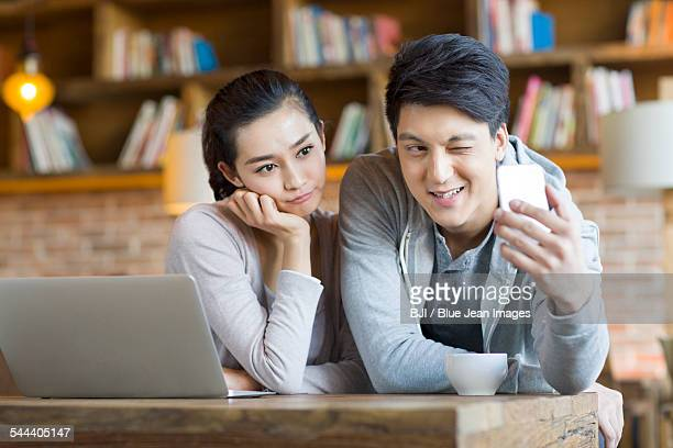 Young couple taking selfie in cafe