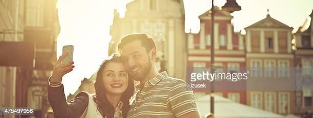 Junges Paar, die Selfies in der Stadt bei Sonnenuntergang