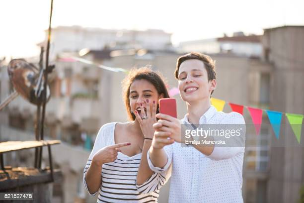 Young couple taking selfie of engagement ring