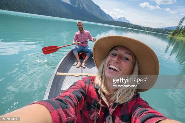 Young couple taking selfie on red canoe at lake