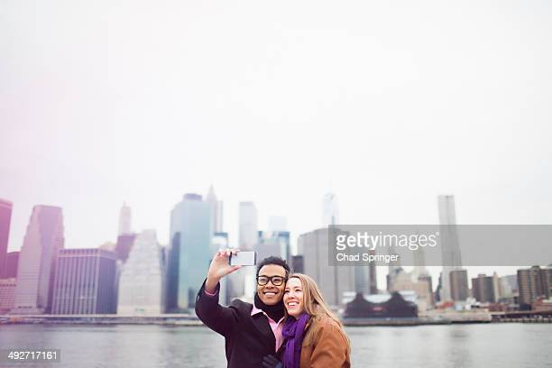 Young couple taking selfie with Manhattan skyline, New York, USA