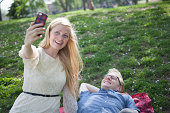 Young couple taking selfie with smartphone in park