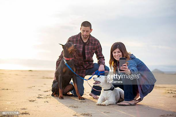 Young couple taking selfies with their pets at the beach