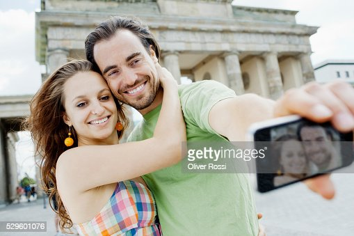 Young couple taking self-portrait photo in city : Stock Photo