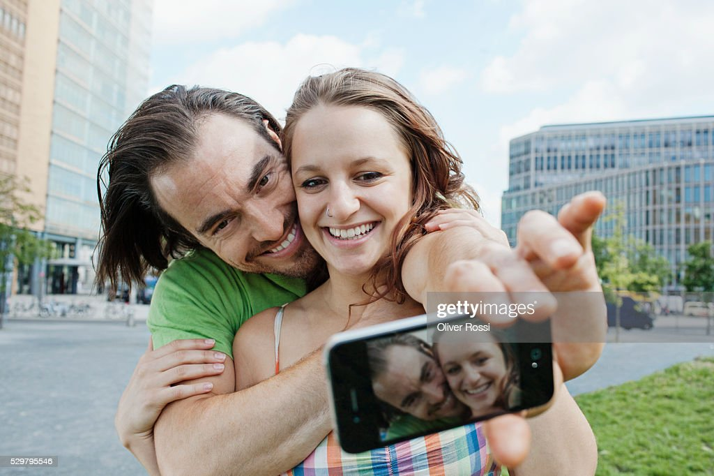 Young couple taking self-portrait photo in city : Foto stock