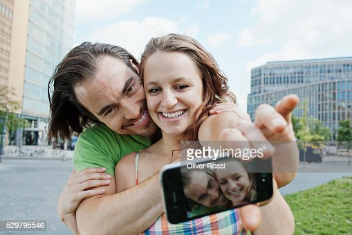 Young couple taking self-portrait photo in city : Stock-Foto