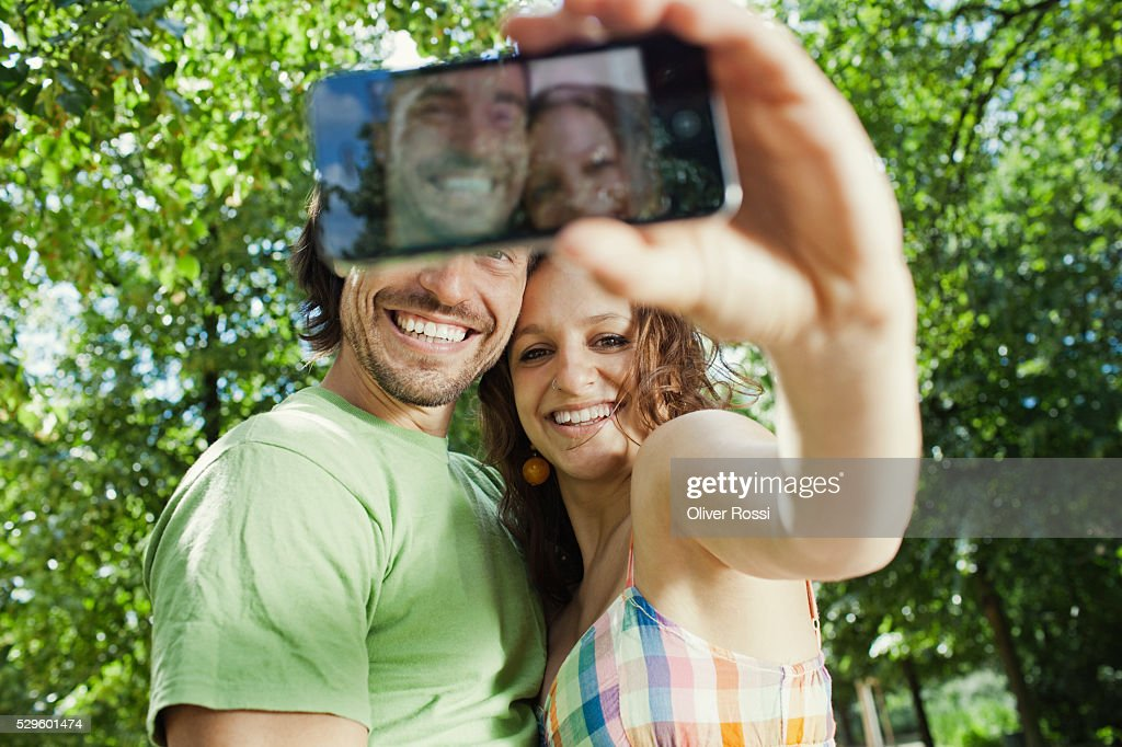 Young couple taking self-portrait photo in park : ストックフォト