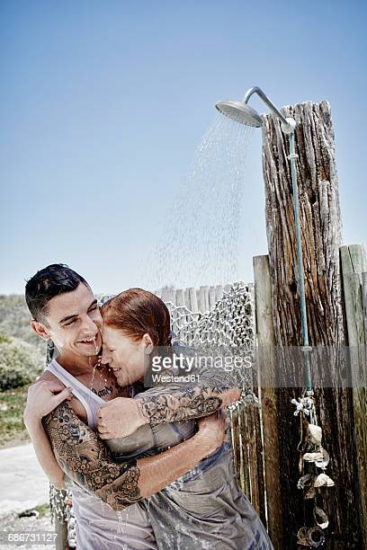 Young couple taking shower on the beach with clothes