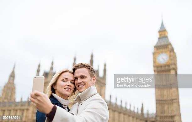 Young couple taking smartphone selfie in front of Big Ben, London, England, UK