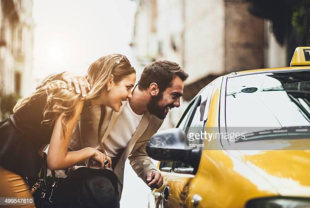 Young couple taking taxi on the street