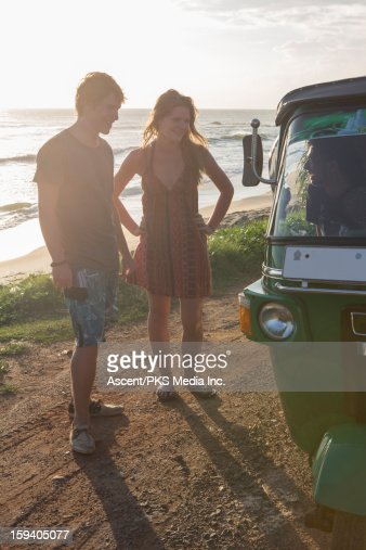 Young couple talk to tuk-tuk driver, surf behind : Stock Photo