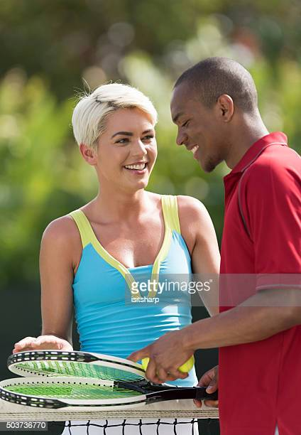 Young couple talking by the net on a tennis court