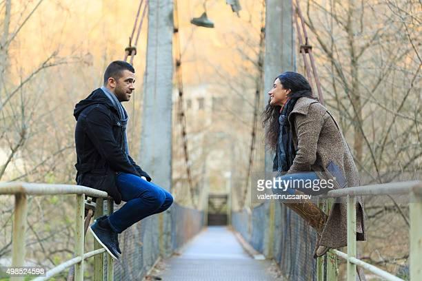 Young couple talking on bridge under autumn sun