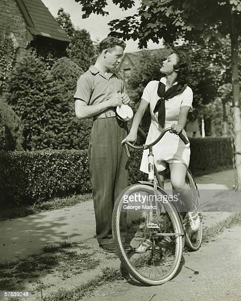 Young couple talking on street, woman on bicycle, (B&W)