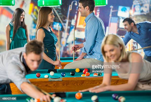Young couple talking playing pool and communicating.