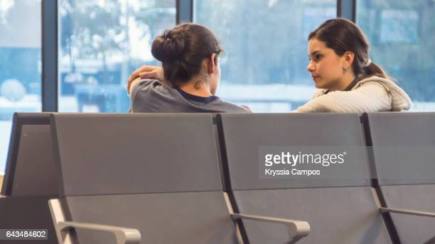 Young couple talking to each other at airport lounge