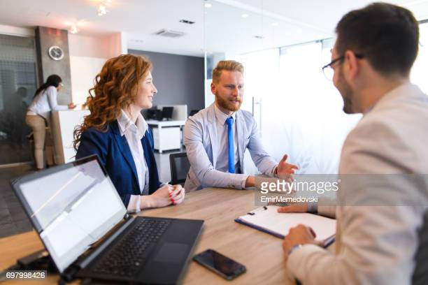 Young couple talking to loan officer