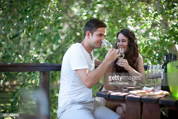 Young couple tasting wine at vineyard bar