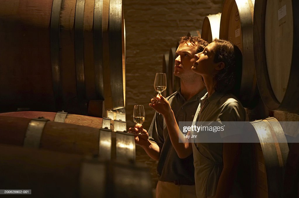 Young couple tasting wine in wine cellar