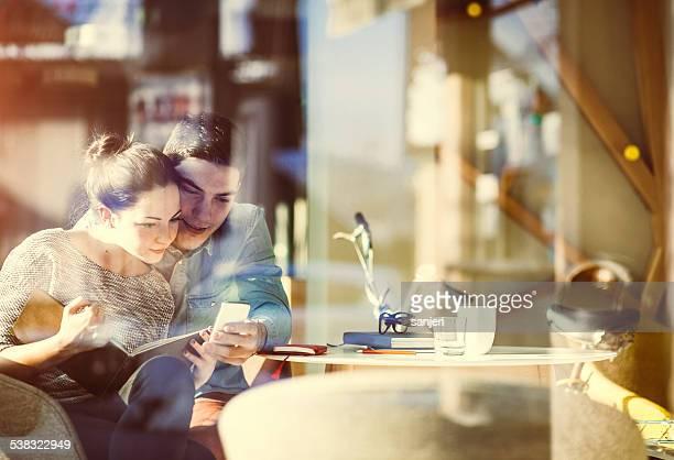 Giovane coppia di messaggistica di testo al bar