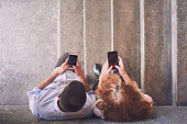 Young man and woman are leaned on wall, standing on stairs, using their smart phones to text messages. Aerial view