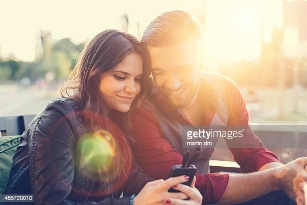 Joven pareja enviando mensajes de texto en smartphone