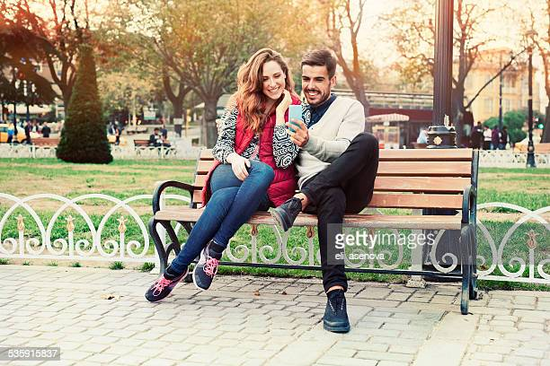 Young couple texting on smartphone