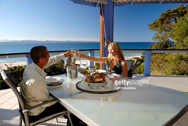 Young couple toasting at dinner in restaurant outside by sea