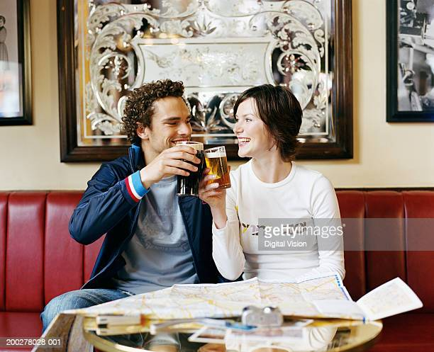 Young couple toasting drinks at pub table, smiling