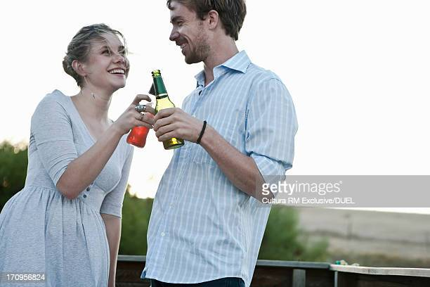 Young couple toasting with beer bottle