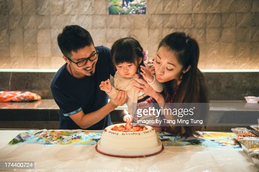 Young couple & toddler blowing birthday candle