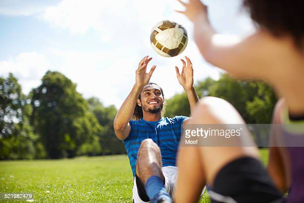 Young couple training with soccer ball in park