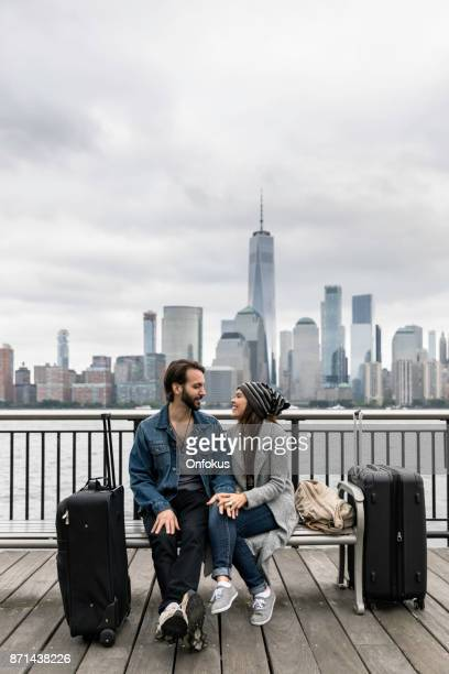 Young Couple Travelers Sitting on Bench and Waiting with Suitcases