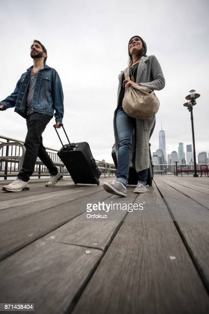 Young Couple Travellers Walking on Wooden Deck with Suitcases