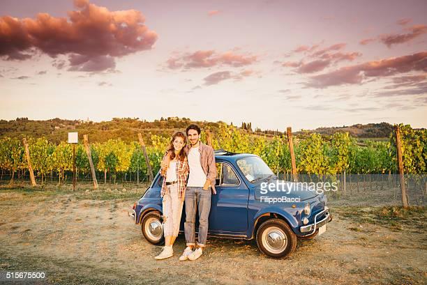 Giovane coppia in viaggio con auto d'epoca