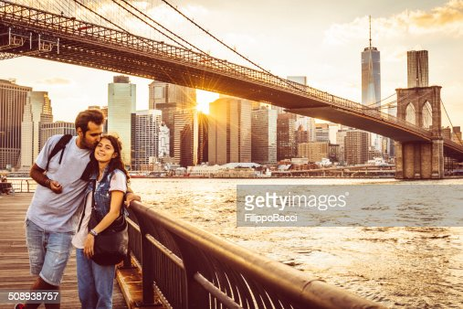 Young Couple Under Brooklyn Bridge at sunset