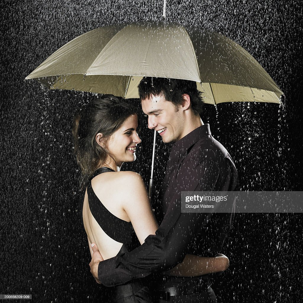 Young Couple Under Umbrella In Rain At Night Side View