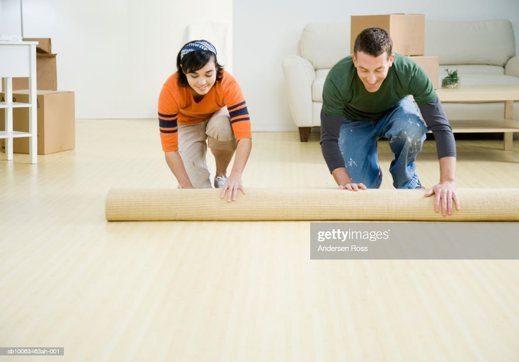 Young couple unrolling carpet in new house : Stock Photo
