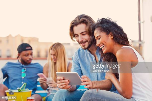 Young couple using a digital tablet at the rooftop