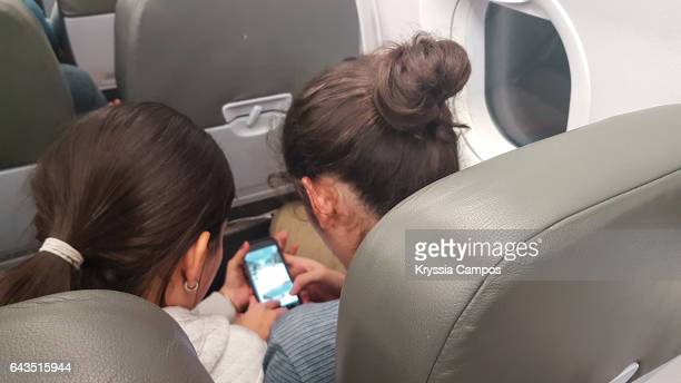 Young couple using a smart phone during a international flight