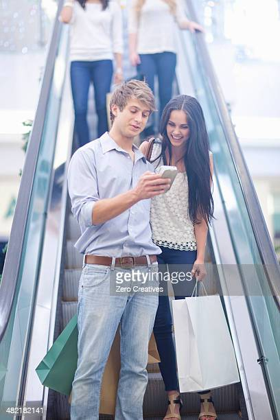 Young couple using cellular phone on escalator